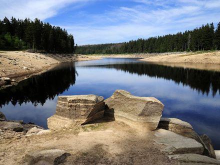 Zusehen ist der Oderteich in Sankt Andreasberg. Im vorderem Bild sind zwei große Steine und um dem Oderteich ist Fels und Wald.