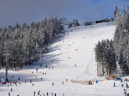 Der obere Abschnitt der Skipiste Hexenritt am Wurmberg ist verschneit und gefüllt mit Skifahrern. An der Seite ist der fahrende Lift zu sehen.