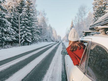 Ein weisses Auto mit Dachgepäckträger fährt über eine verschneite Straße. Aus dem hinteren Fenster lehnt eine Frau in einer roten Jacke.