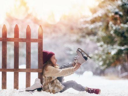 Ein kleines Mädchen sitzt auf schneebedecktem Boden angelehnt an einen Zaun und zieht sich Schlittschuhe an. Im hintergrund scheint die Sonne durch die Bäume.